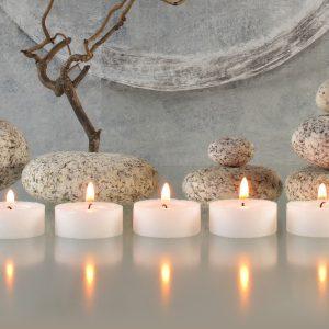 Gesteck mit Zweigen, Steinen und Kerzen